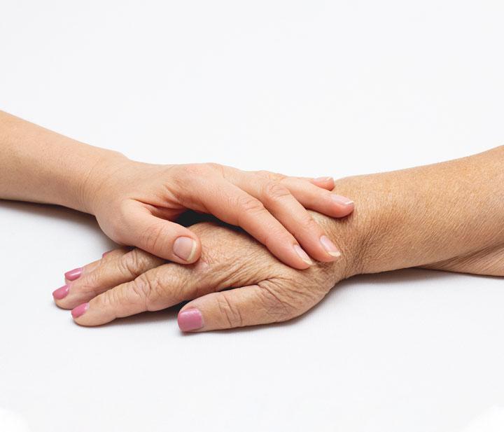 Mano sobre mano de persona dependiente - Acompañamiento en la vejez en Extremadura. Ayuda a Domicilio, Promoción a la Autonomía, residencias, formación